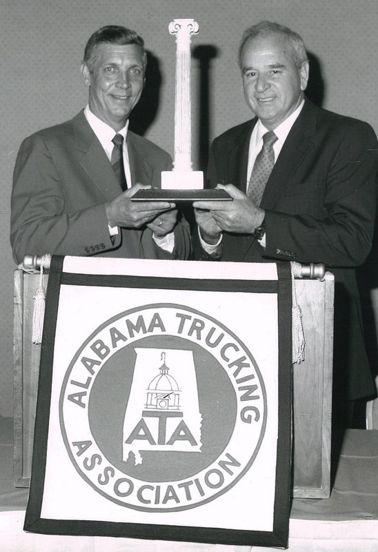 Dempsey Boyd, at right, receives the Alabama Trucking Association's H. Chester Webb Award from the trucking association's board chairman, Bill Harris with Fruehauf Trailer Co. Dempsey received the award in 1987 for lifetime achievement and service to the trucking industry. In 2010, Dempsey's daughter Gail Cooper became the first woman in the organization's 76-year history to be elected as chairman of the board of directors. Four years later, Gail was also honored with the same lifetime achievement award her father earned 27 years earlier.