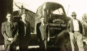 Cecil Boyd, at left, and his brothers Hilly and Dempsey stand next to a tractor their father, William Nickey Boyd, right, operated. Following World War II, the Boyd brothers drove trucks for 10 years before starting their own company: Boyd Brothers in 1956.
